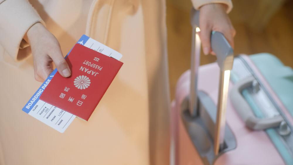 日本のパスポートを差し出す、キャリーバッグを引いている女性