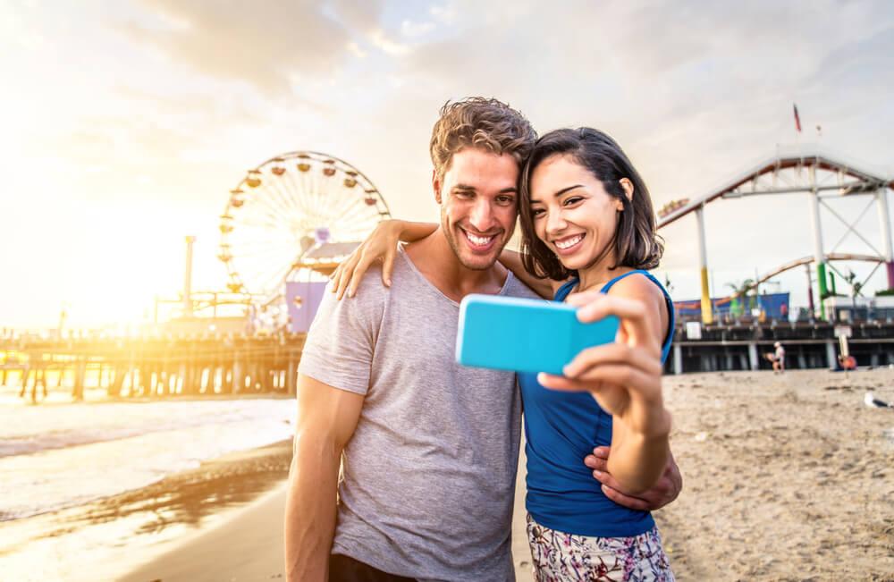 観覧車を背景に写真を撮るカップル