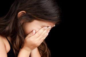 跛行婚によって親と会えなくなった女の子が顔を覆って泣いている