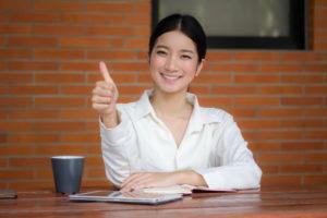 机に向かってOKサインを出す中国人女性