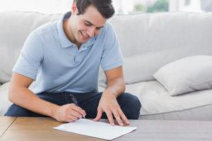 男性が楽しそうに婚姻にかかる書類を作成している