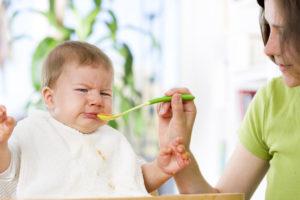 ぐずる赤ちゃんに、笑顔でご飯をあげる外国人女性