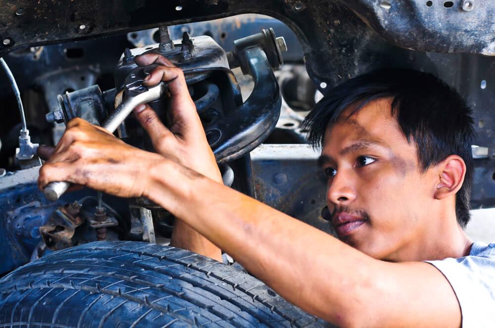 オイルに汚れながら車の整備を進める東南アジアの男性