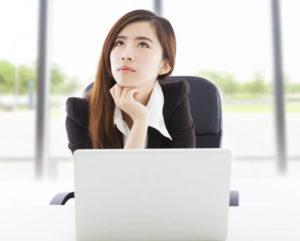 パソコンの前で困った表情を浮かべる中国人女性