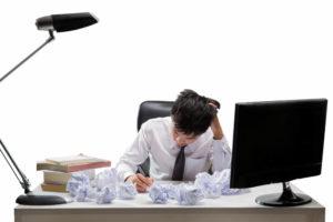 デスクの上に書類のゴミが山のように溜まって頭を抱えている男性