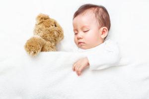 跛行婚であるため、国籍が不安定になっている赤ちゃんが、何も知らずにお人形さんとすやすや眠っている