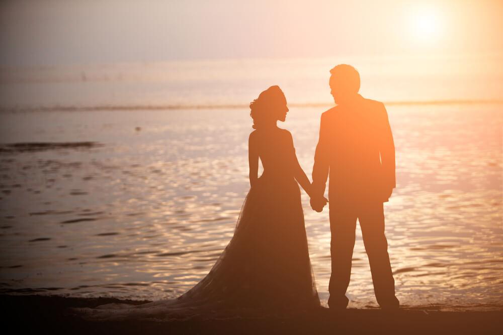 夕焼けの海岸で手をつなぐカップルのシルエット