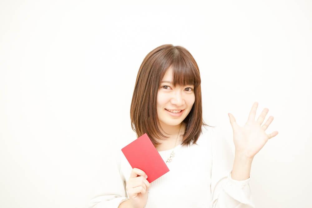 日本のパスポートをもって、こちらに手を振る日本人女性