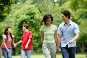 公園内で手をつないで歩く東洋人カップルたち