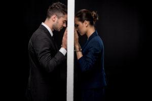 男女の間に壁があり、お互いが壁におでこをつけて嘆いている