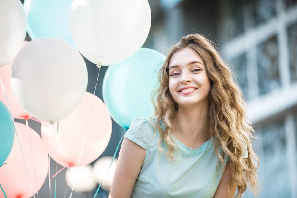 たくさんの風船を背景に、こちらへ笑顔を投げかける外国人女性