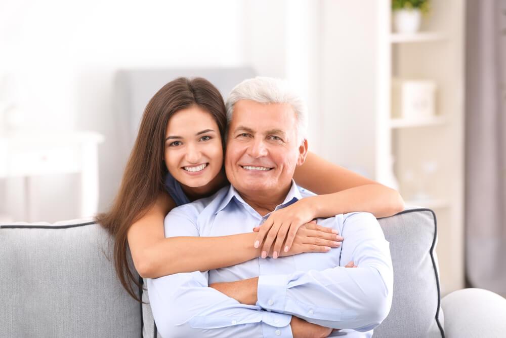 親子ほど年が離れたカップル。女性が男性に抱きついている