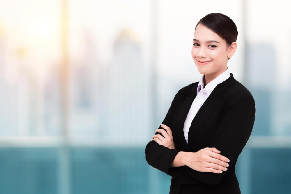 近代的オフィスの窓際で、腕を組んでこちらに微笑みかけるスーツ姿の外国人女性