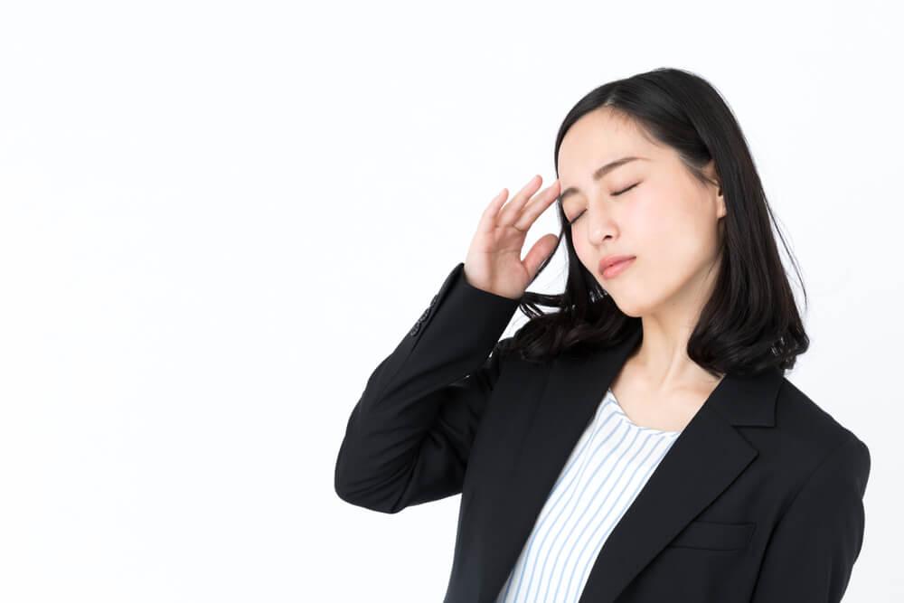 こめかみをおさえて悩む、リクルートスーツ姿のアジア人女性