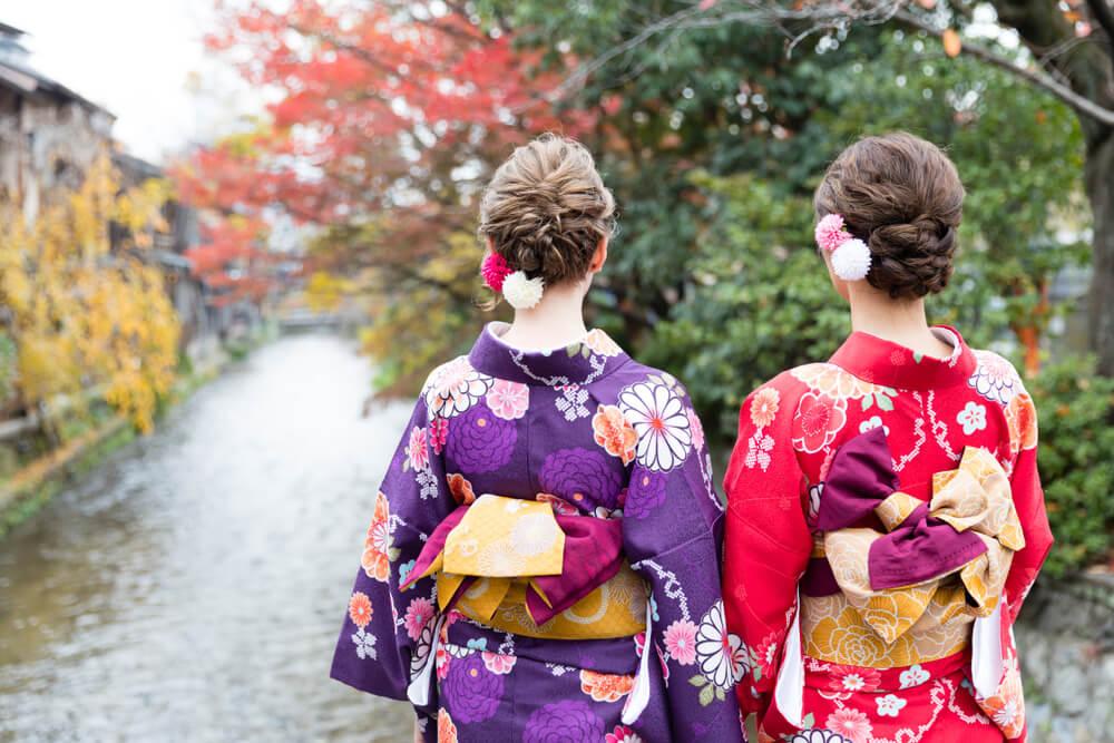 日本の川の流れを眺めながら、日本国籍を選択しようと決意する着物姿の外国籍と日本国籍を持つ重国籍の女性