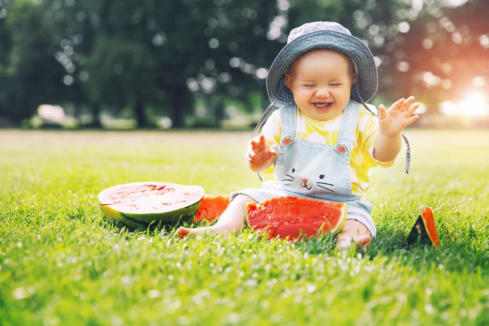一人で楽しそうにスイカで遊ぶ赤ん坊(単独戸籍をイメージ)