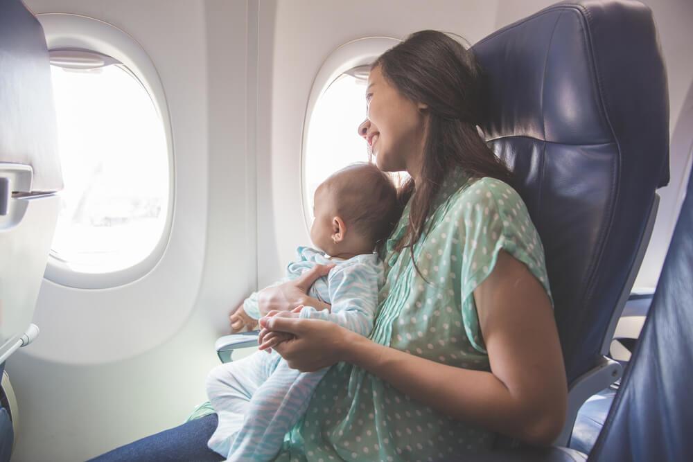 お母さんの膝上に座って飛行機に乗る赤ちゃん