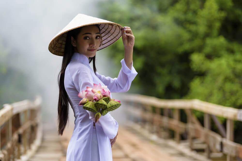 アオザイを着てこちらに花束を渡そうとしている若いベトナム人女性