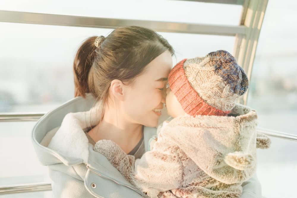 赤ちゃんとおでこをくっつけている若いアジア人のお母さん