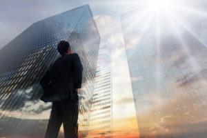オフィスビル群を見上げる高度専門職の外国人材